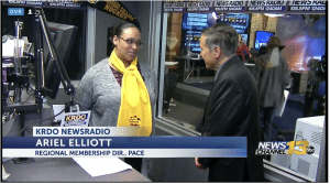 woman in yellow scarf being interviewed on TV